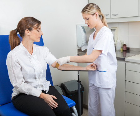 Foto de Nurse Preparing Businesswoman For Blood Test - Imagen libre de derechos
