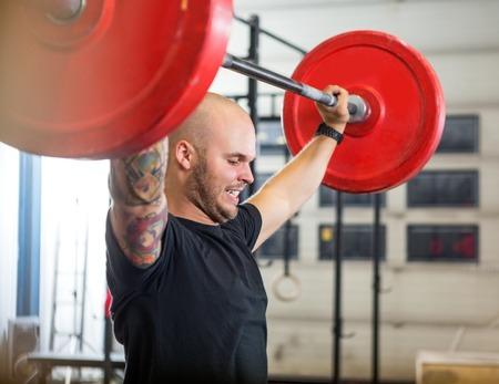 Photo pour Athlete Exercising With Barbell At Gym - image libre de droit