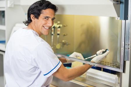 Foto de Happy Technician Experimenting In Laboratory - Imagen libre de derechos
