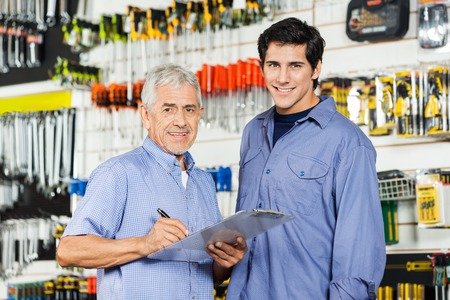 Photo pour Father And Son Preparing Checklist In Hardware Store - image libre de droit