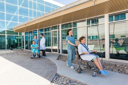Foto de Medical Team With Patients On Wheelchairs At Hospital Courtyard - Imagen libre de derechos