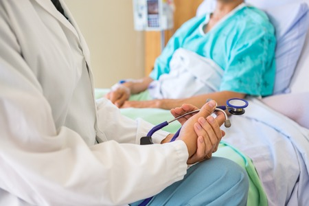 Photo for Female Doctor Sitting With Patient On Hospital Bed - Royalty Free Image