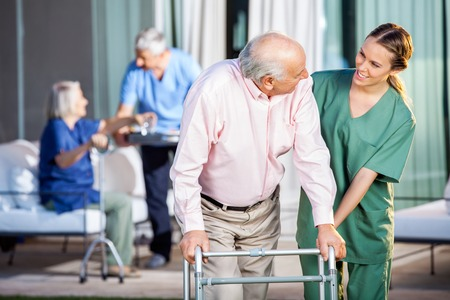 Photo pour Happy Caretaker Assisting Senior Man In Using Zimmer Frame - image libre de droit