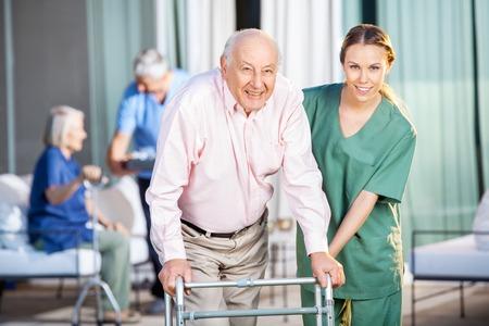 Foto de Female Caretaker Helping Senior Man In Using Zimmer Frame - Imagen libre de derechos