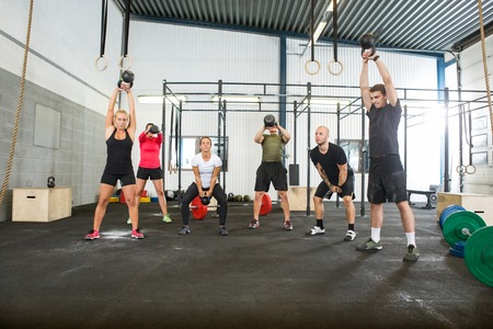 Photo for Athletes Lifting Kettlebells in Cross Fitness Box - Royalty Free Image