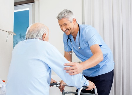 Photo pour Caretaker Helping Senior Man To Use Walking Frame - image libre de droit