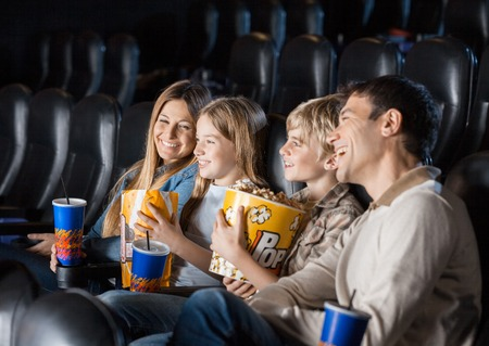 Photo for Family Enjoying Movie In Theater - Royalty Free Image