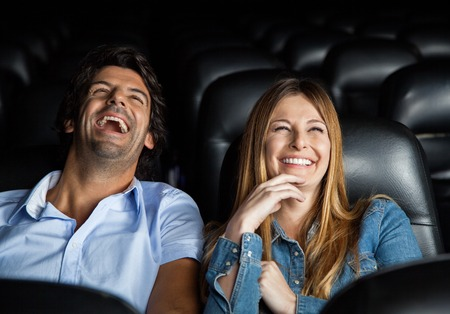 Foto de Couple Laughing While Watching Film In Theater - Imagen libre de derechos