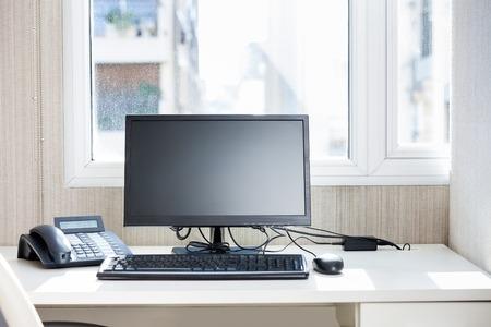 Foto de Computer And Landline Phone On Desk - Imagen libre de derechos