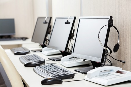 Foto de Computers With Headphones On Desk - Imagen libre de derechos