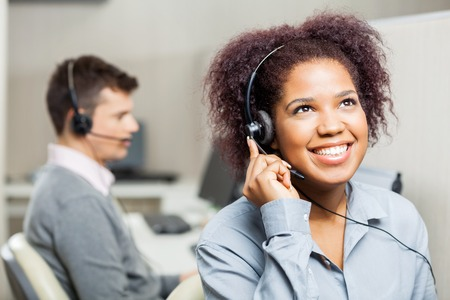 Photo pour Happy Female Call Center Agent Using Headset In Call Center - image libre de droit