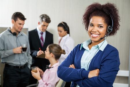 Photo pour Happy Female Customer Service Representative Standing Arms Cross - image libre de droit