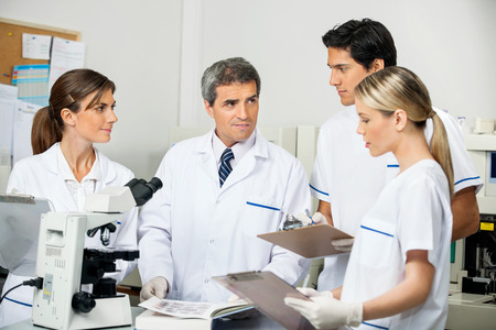 Foto de Mature male scientist with students taking notes in medical laboratory - Imagen libre de derechos