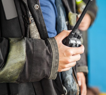 Midsection of firefighter holding walkie talkie at fire station