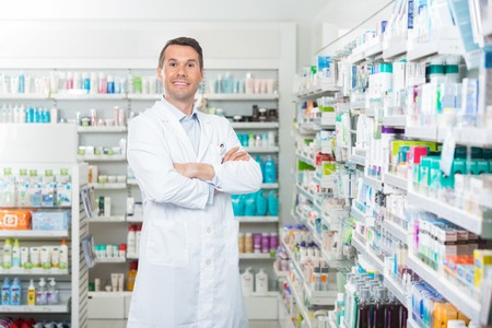 Foto de Portrait of smiling mid adult male pharmacist standing arms crossed in pharmacy - Imagen libre de derechos