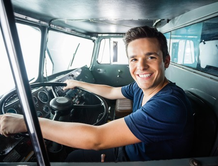 Photo for Portrait of happy young fireman driving firetruck at station - Royalty Free Image