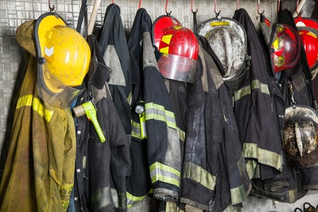 Photo pour Firefighter suits and helmets hanging at fire station - image libre de droit
