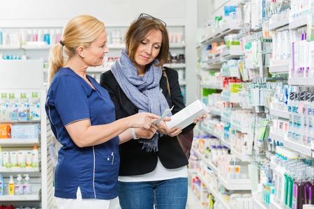 Foto de Mature chemist explaining product details to female customer in pharmacy - Imagen libre de derechos