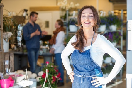 Photo pour Portrait of smiling female owner with customers in background at flower shop - image libre de droit