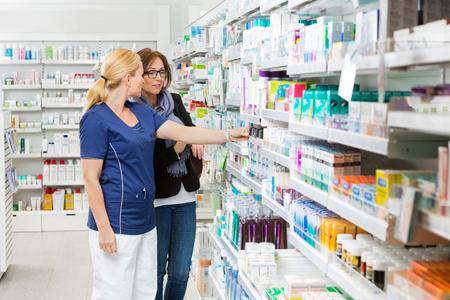 Foto de Female pharmacist removing product for customer from shelf in pharmacy - Imagen libre de derechos