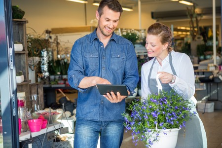 Photo pour Male customer using digital tablet while standing by florist holding potted plant in shop - image libre de droit