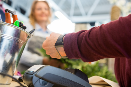 Foto per Cropped image of female customer paying through smart watch at flower shop - Immagine Royalty Free