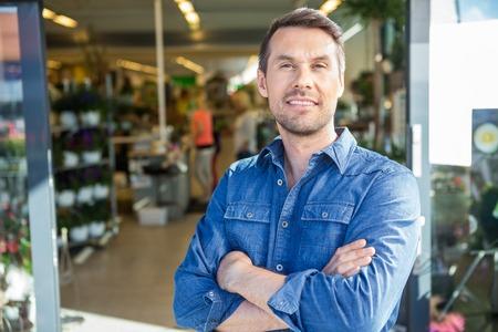 Photo pour Portrait of confident man with arms crossed standing outside flower shop - image libre de droit