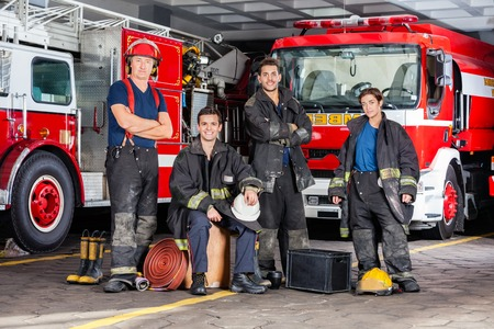 Portrait of confident firefighters with equipment against trucks at fire station