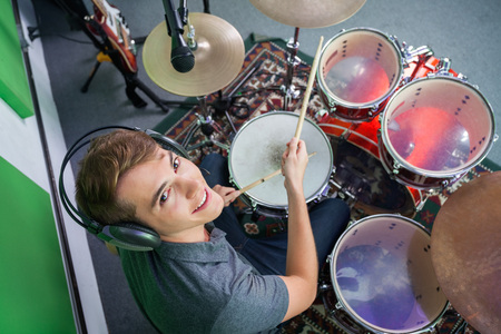 Photo for High angle portrait of smiling male drummer wearing headphones while performing in recording studio - Royalty Free Image