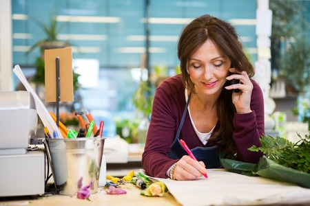 Photo for Female florist using mobile phone while writing on paper in flower shop - Royalty Free Image