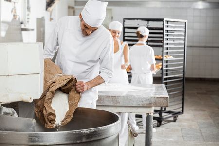 Foto per Mature male baker pouring flour in kneading machine at bakery - Immagine Royalty Free