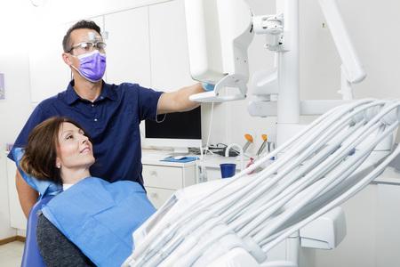 Photo pour Mid adult male dentist explaining xray to female patient in clinic - image libre de droit