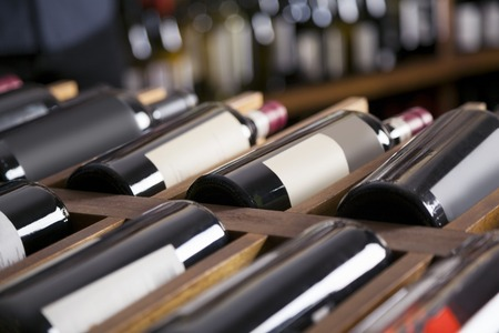 Photo for Red wine bottles displayed on shelves in supermarket - Royalty Free Image