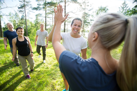 Photo for Women Giving High-Five While Friends Walking At Forest - Royalty Free Image