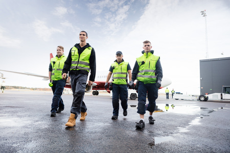 Photo for Low Angle View Of Workers Walking On Runway - Royalty Free Image