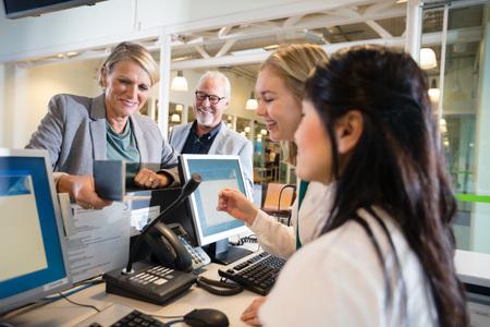 Foto de Businesswoman Holding Passport While Staff Working At Airport - Imagen libre de derechos