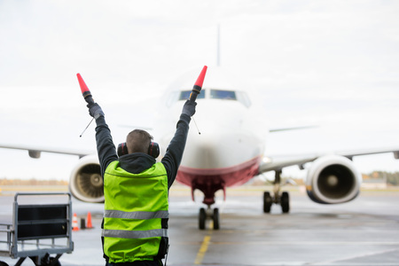 Foto de Ground Crew Signaling To Airplane On Runway - Imagen libre de derechos