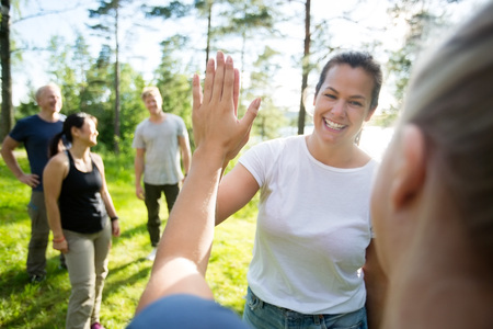Photo pour Women Giving High-Five While Friends Standing At Forest - image libre de droit