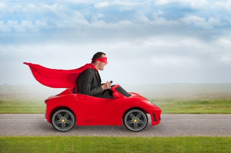 Photo for superhero man driving a red toy racing car at speed - Royalty Free Image