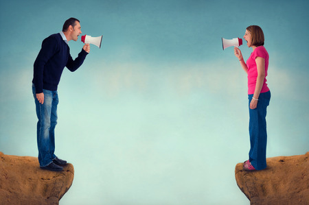 Foto per man and woman conflict concept with bullhorn and crevasse - Immagine Royalty Free