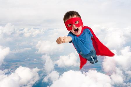 Foto de superhero boy child flying upwards through the clouds - Imagen libre de derechos