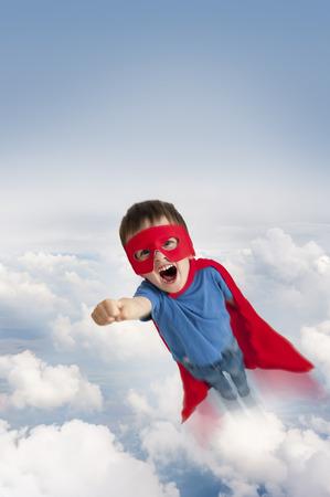 Photo pour superhero boy flying in the sky through clouds - image libre de droit