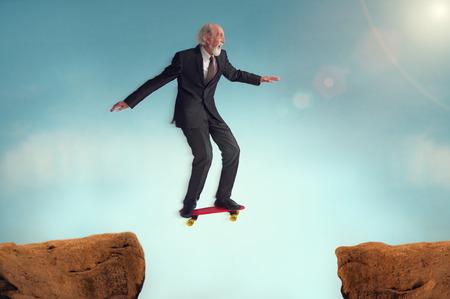 Foto de senior man enjoying the risk of a jumping challenge on skateboard - Imagen libre de derechos