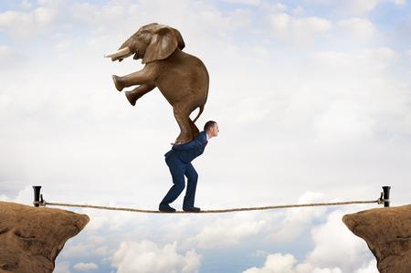Photo pour business challenge concept businessman carrying an elephant across a tightrope chasm - image libre de droit
