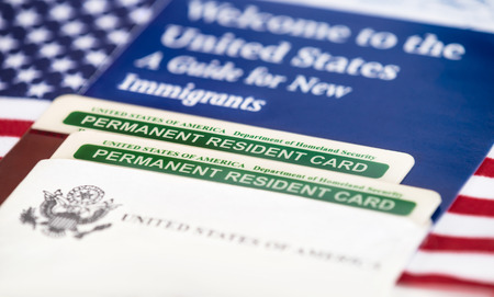 Photo pour United States of America permanent resident cards, green card, with US flag on the background. Immigration concept. Closeup with shallow depth of field. - image libre de droit
