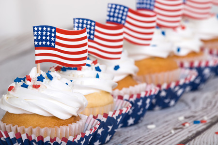Photo for Row of patriotic cupcakes with sprinkles and American flags on vintage background - Royalty Free Image