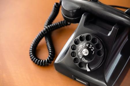 Photo pour Old fashioned retro rotary dial phone on wooden desk, closeup - image libre de droit