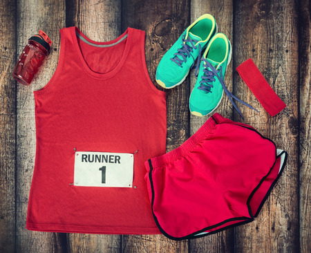 Photo pour Running gear laid out ready for a race day, rustic wooden background - image libre de droit