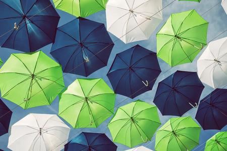 Foto de Group of green, blue, and white umbrellas against blue sky - Imagen libre de derechos
