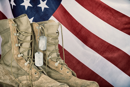 Foto de Old combat boots and dog tags with American flag in the background. Vintage filter effects. - Imagen libre de derechos